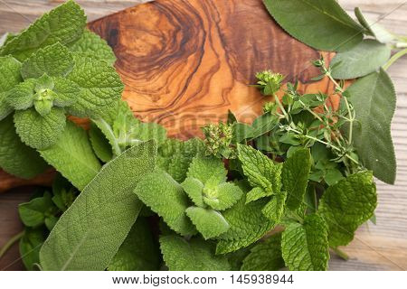 Aromatic green herbs and spices on a wooden background.