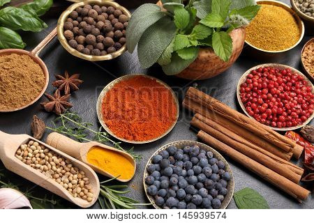 Spices and herbs on black ceramic background.. Food and cuisine ingredients.