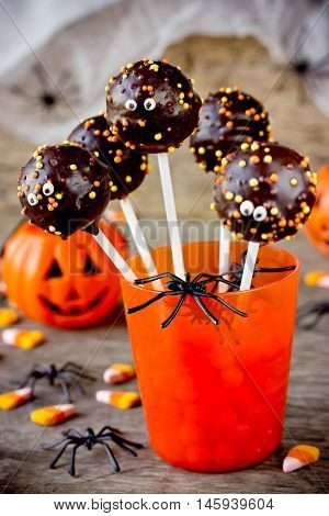 Halloween pop cakes in orange glass for Halloween party vertical background selective focus
