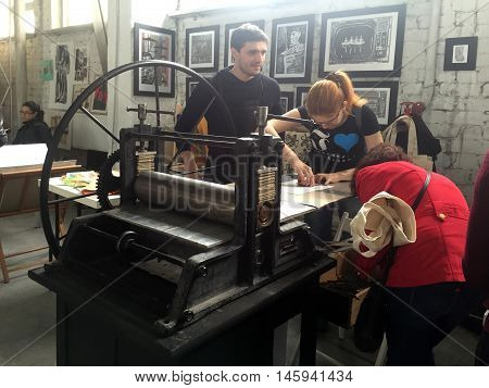 KIEV, UKRAINE - APRIL 9, 2016: Young people work on old printing machine on craft workshop, Kiev, Ukraine.
