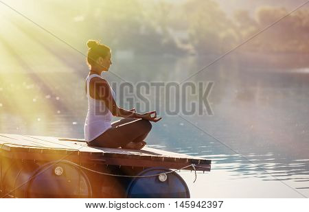 Woman doing yoga on a rock at the quarry with the lake - beautiful lights in morning time. Shallow depth of focus, post lights.