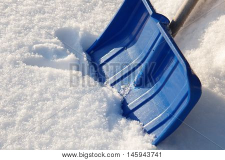 A blu snow shovel on snowy background