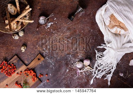 Bread, bread sticks and buns with ingredients over rustic background. Food frame, view from above, copy space.