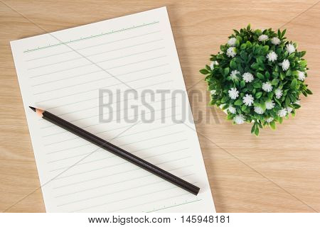 Open blank white paper notebook with copyspace and a pen lying on a white desk, view from above / for your text or message / top view