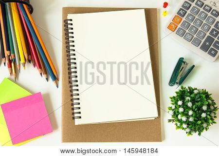 brown paper blank and paper note, color pencil, calculator, pen on white desk with copyspace / for your text or message, artwork / view from above, top view / business, office supplies concept