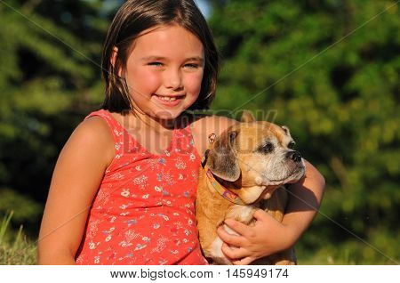 Portrait of happy little girl hugging her puppy