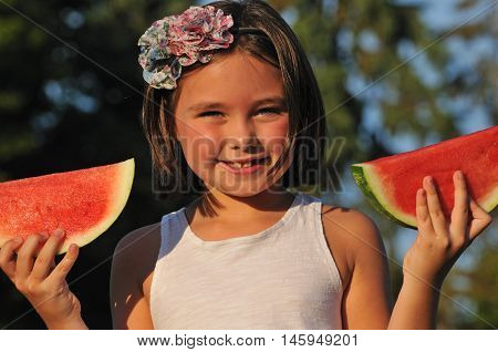 Happy healthy girl holding up slices of fresh watermelon