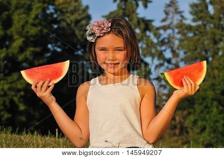 Happy little girl holding up slices of fresh sweet watermelon