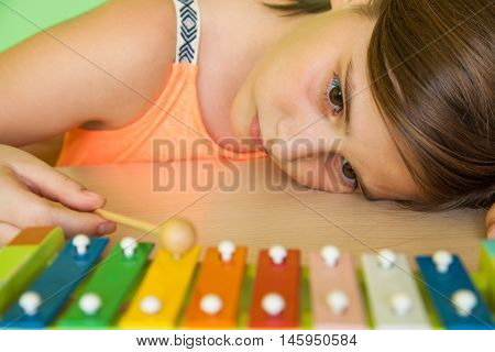 sad little girl playing color metallophone and hearing sound