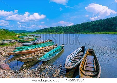 Wooden boats moored to the bank of the river. Beautiful river landscape.