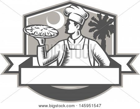 Illustration of a pizza chef baker serving holding pizza looking to the side viewed from front set inside shield crest with moon and palmetto tree in the background done in retro style.