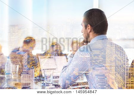 Business team meeting in conteporary corporate office. Businessman working on laptop computer. New Your city lights reflection in window. Business success concept.