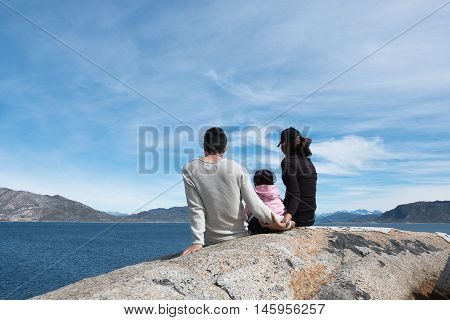 Parents Happy Family Holding hands sitting on a rock overlooking the turquoise sea. Skies In a happy holiday.
