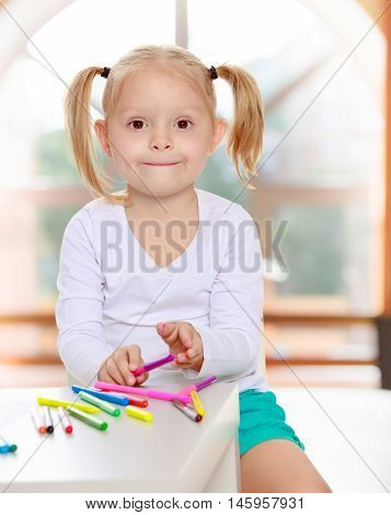 Pretty little blonde girl drawing with markers at the table.Girl holding in hands a pink marker.The concept of pre-school education of the child among their peers . in gaming room with a large arched window.