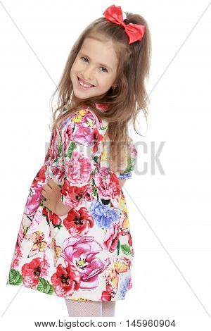 Smiling little girl with a long ponytail down to his shoulders, and a red bow on her head, in a beautiful summer dress. The girl turned sideways to the camera. Close-up - Isolated on white background