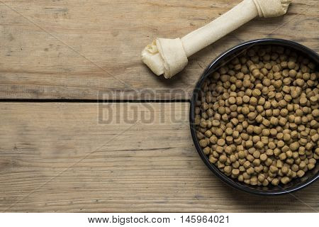Dog bone and dog food on wood table