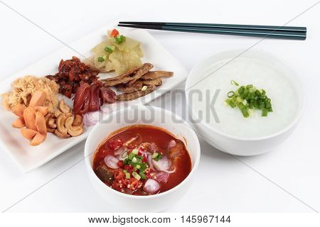 Rice gruel and  side dish  on white background. (Dried shredded pork,Chinese sausage,crispy fish,sausage, fried baby clams,sliced red onion,pickle Chinese cabbage ,Spicy sardine salad and shallots )