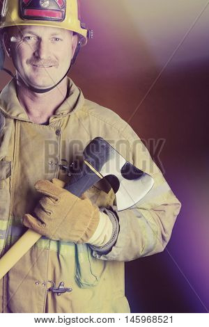 Smiling firefighter in uniform holding axe