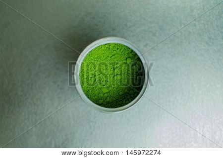 Matcha - Japanese green tea powder in a can on silver background