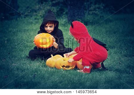 Children in scary costumes with pumpkins. Boys in halloween outfit playing in the garden