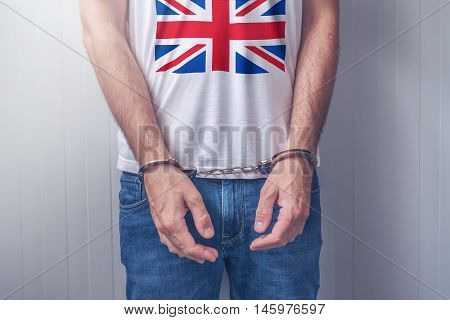 Arrested man with cuffed hands wearing shirt with United Kingdom flag. Unrecognizable male person in jeans with handcuffs held in police station for being suspected of a crime.