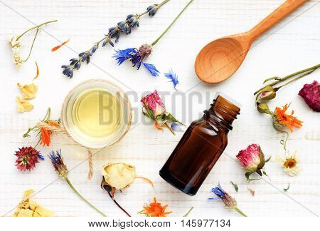Essential oil, medicinal plant mix, herbal skincare ingredients. Top view Aroma dropper bottle, dried leaves,flowers,herbs, extract sample,spoon. poster