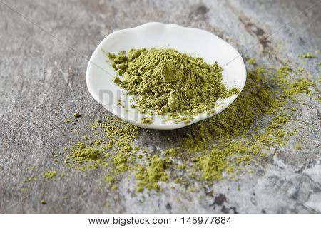 Matcha Tea On A Small White Plate. Gray Background.