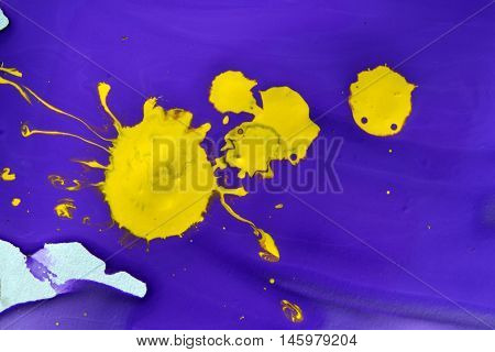 violet gouache paint and a yellow blotch in the middle close-up. Abstract background purple and yellow liquid paint. Artistry, art, creativity,