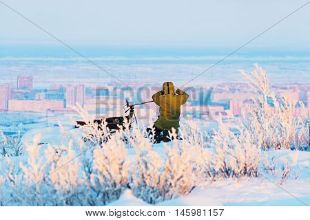 Man with photo camera on tripod taking timelapse photos winter panorama of the city.. Poor lighting conditions.