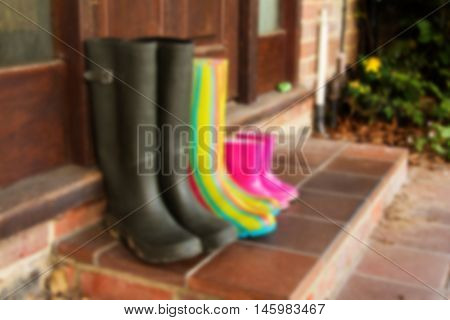 Colourful Wellington Boots Left On A Doorstep Out Of Focus.