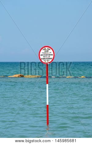 A red and white warning beach sign in the water of the Mediterranean Sea in Italy.