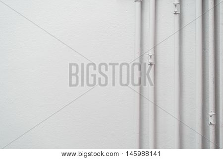 A pipe across the white walls in soft light