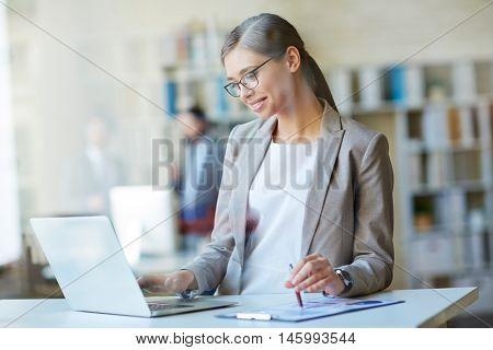 Portrait of young intelligent woman taking her internship in business, standing in office space at her desk with laptop computer, preparing data for analysis