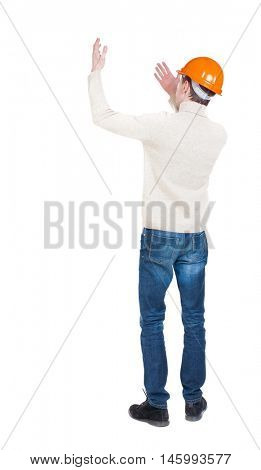 Back view of  pointing young men in helmet. Young guy  gesture. Rear view people collection.  backside view of person.  Isolated over white background. Foreman beckoning someone to her.