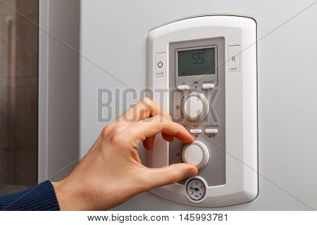 Men hand regulate temperature on 55 degree in control panel of DHW.