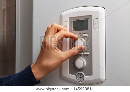Men hand regulate low temperature on 35 degree in control panel of central heating.