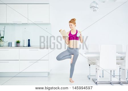 Smiling red haired woman in bright sportswear exercising, reading and drinking coffee at the same time in spacious white kitchen room