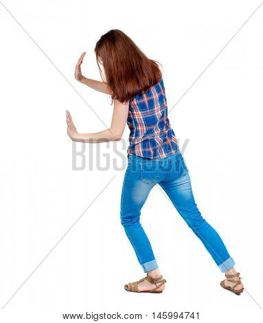 back view of woman pushes wall. backside view of person. Girl in plaid shirt shoves something in the side.