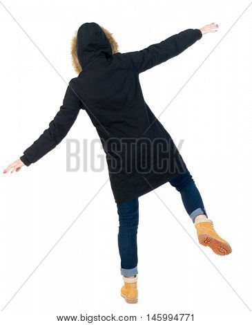 Back view woman in winter jacket Balances waving his arms. Standing young girl in parka. Girl in warm winter black jacket falls to the side.
