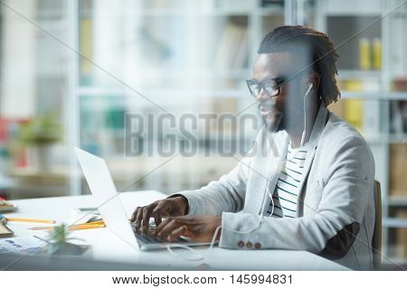 Self-assured stylish African-American businessman in glasses typing at laptop computer and listening to music in earphones, during working day in modern office behind glass wall