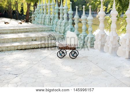 Doll's Pram. Vintage Doll Stroller Placed On The Stairs To A Beautiful Lake. Retro Cart Dolls Made O