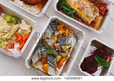 Healthy food delivery, daily ration. Take away of natural organic low carb diet. Fitness nutrition in foil boxes. Top view, flat lay with copy space at white wood. Mackerel fish, vegetables and fruits