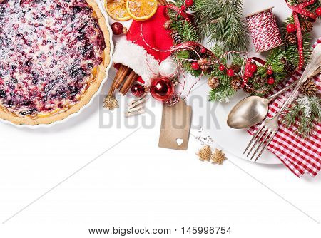 Christmas food concept - wild berry pie with plate fork and spoon with christmas decoration top view isolated empty space