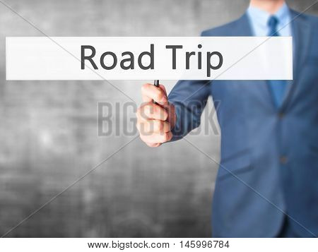 Road Trip - Businessman Hand Holding Sign
