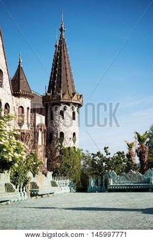 Beautiful Old Fairy-tale Castle Near Burgas, Bulgaria. Walls Of The Castle, Green Flower Garden. Sto
