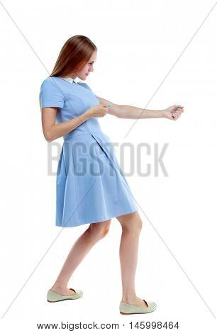 back view of standing girl pulling a rope from the top or cling to something. Isolated over white background. Skinny girl in a blue dress and holding on to the rope.