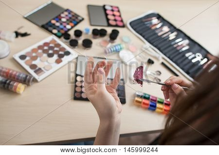 Colorful cosmetics on stylist workplace. Stylish ladies lifestyle accessories. Variety of makeup tools, palettes and brushes. Artist hand smearing lipstick