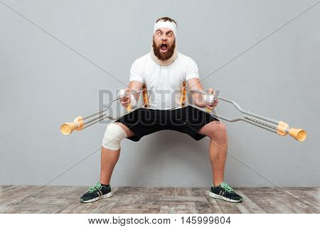 Freaky crazy young man playing with crutches and shouting over white background