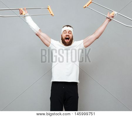 Cheerful excited young man raising crutches and celebrating success over white background