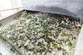 Glass particles for recycling in a machine in a recycling facility. Different glass packaging bottle waste. Glass waste management. Glass recycling is the process of waste glass into usable products. poster